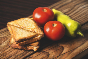Grilled sheese sandwiches with vegetables - pepper and tomatos on a wooden table