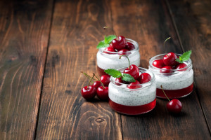 Chia seeds yogurt pudding, jelly and fresh sweet cherries in jar, selective focus