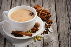 Indian masala chai tea. Spiced tea with milk on the rustic wooden table. Selective focus, copy space.