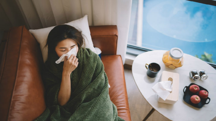 sick woman with flu laying on couch