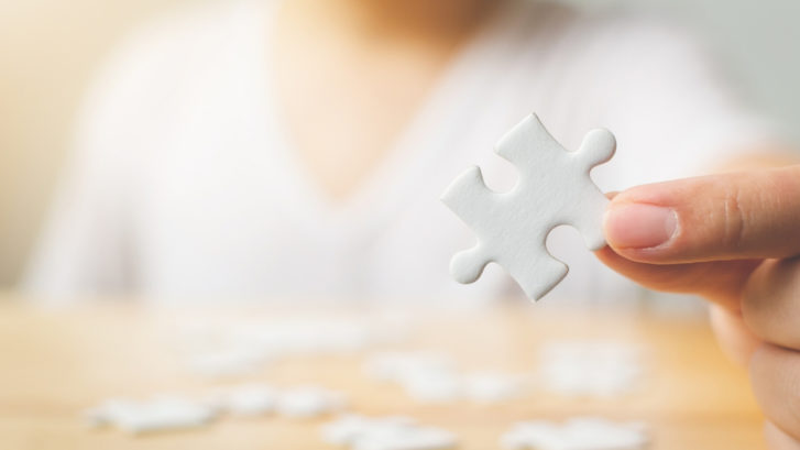 person holding blank puzzle piece
