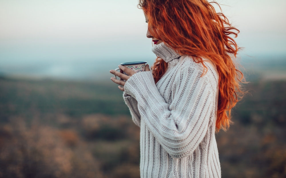 Long hair red head holding tea