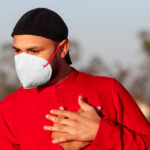 A man wearing a red shirt and a mask to protect from COVID clutches his chest with both hands.
